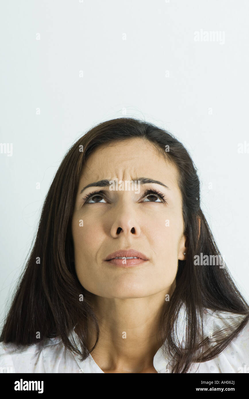 Woman furrowing brow, looking up, portrait - Stock Image