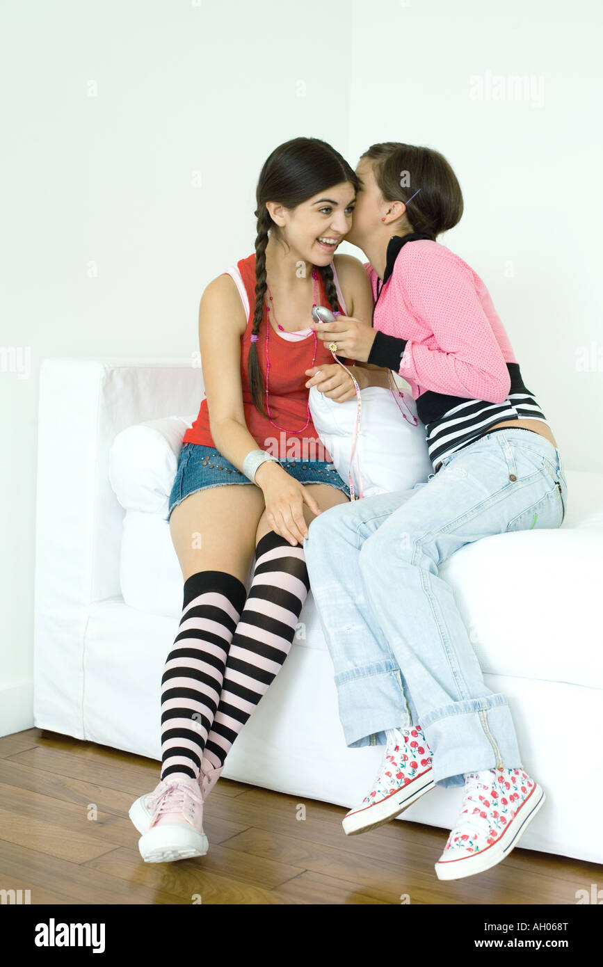 Two young female friends sitting on sofa, one whispering to the other - Stock Image