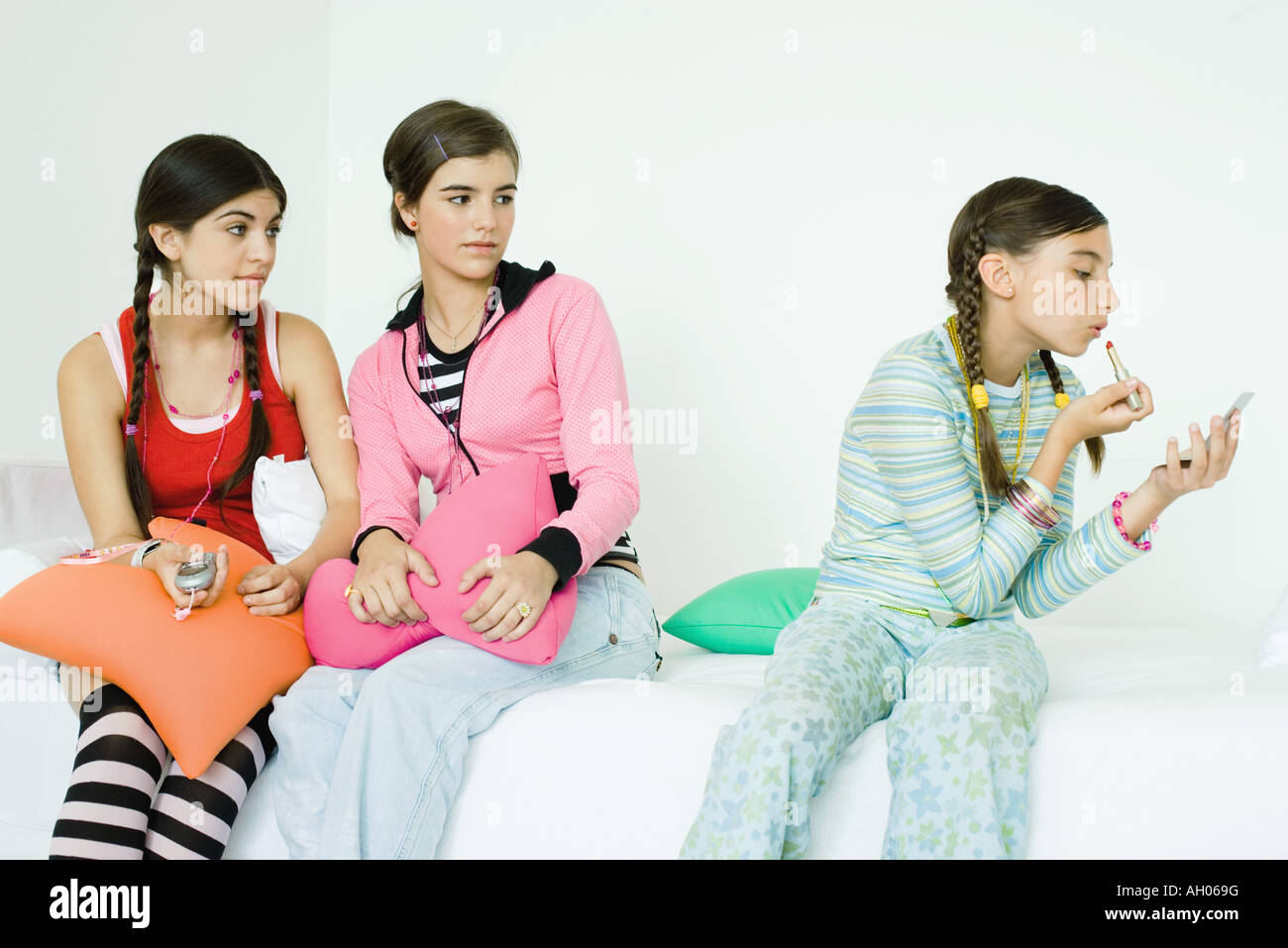 Three young female friends sitting on sofa, two watching younger girl putting on make-up - Stock Image