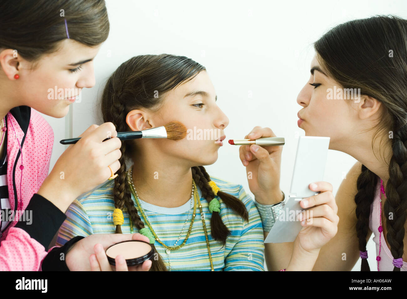 Two young female friends putting make-up on younger girl - Stock Image