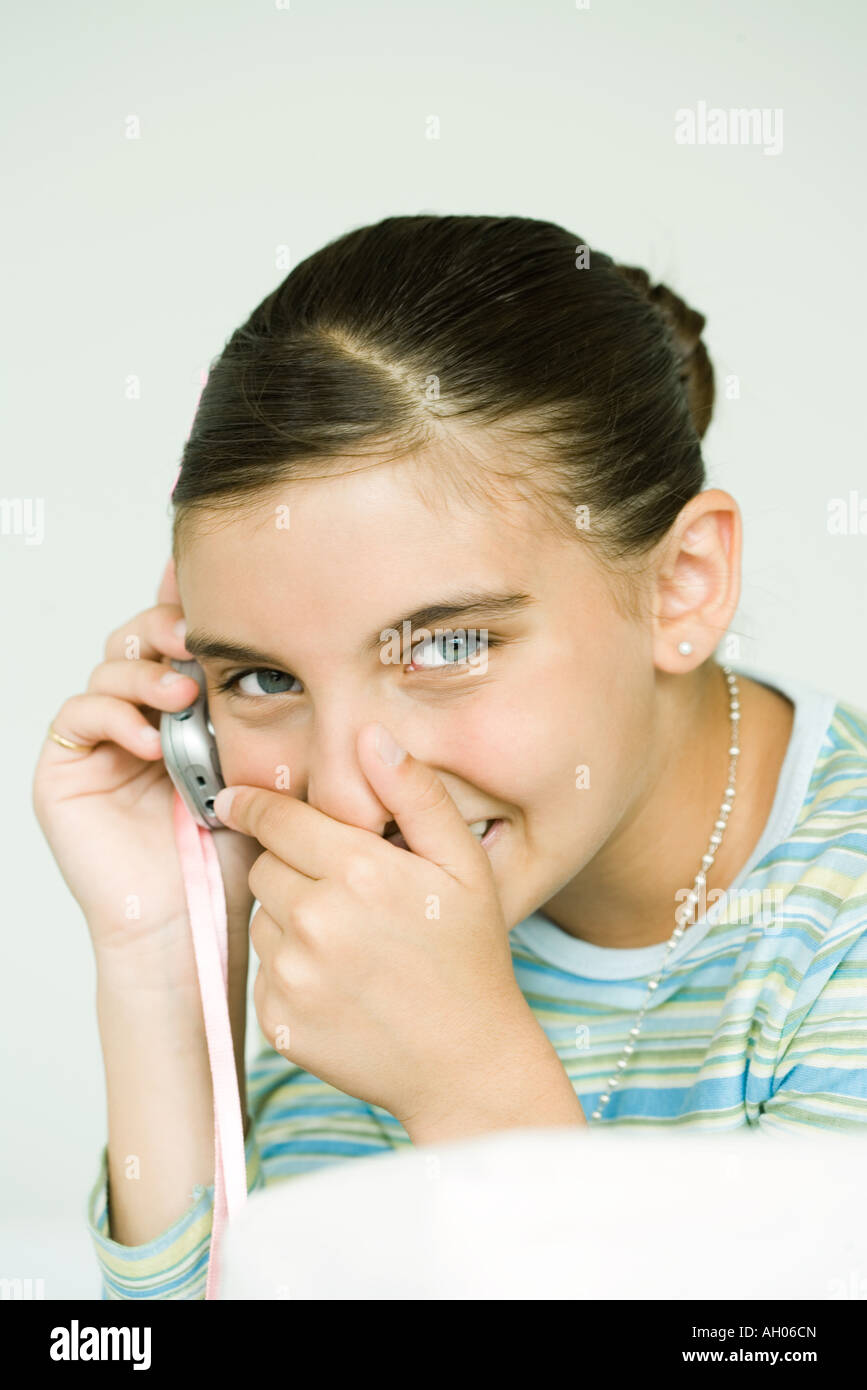 Girl talking on cell phone, covering mouth and giggling - Stock Image