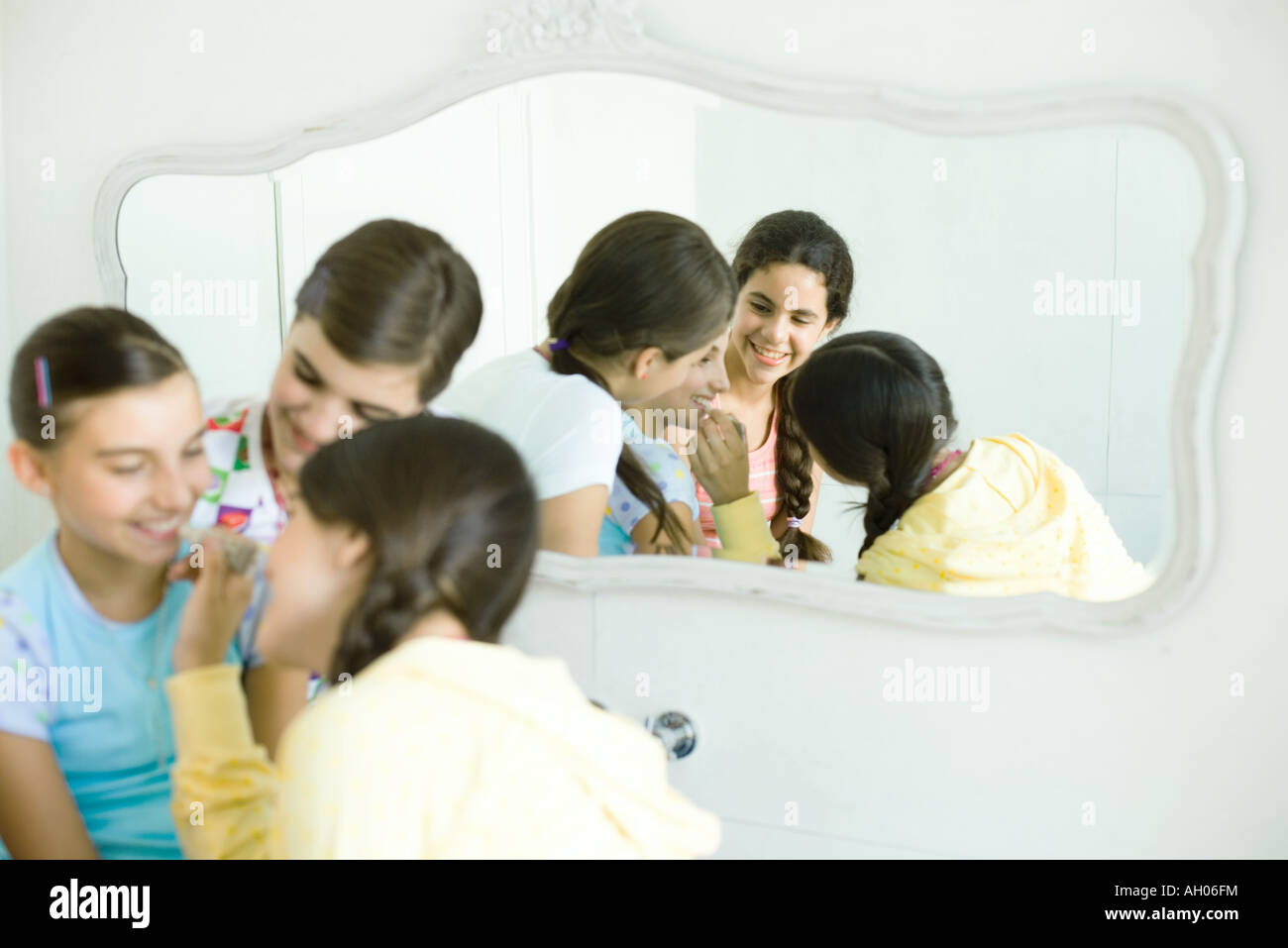 Young female friends putting make-up on younger girl - Stock Image