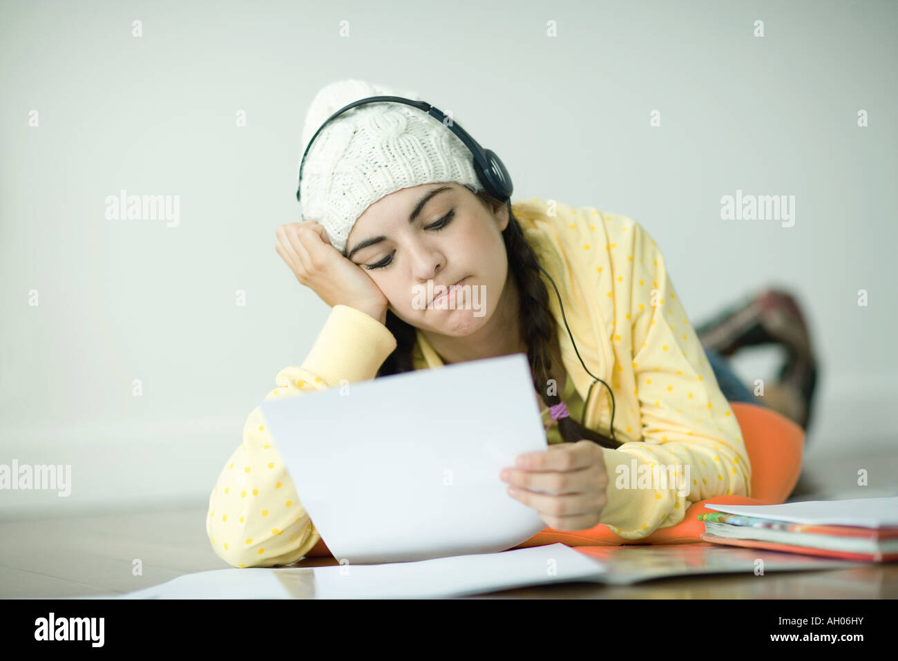 Young woman lying on floor listening to headphones and doing homework - Stock Image