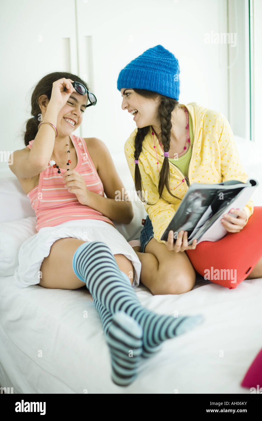 Two young female friends looking in magazine together, laughing - Stock Image