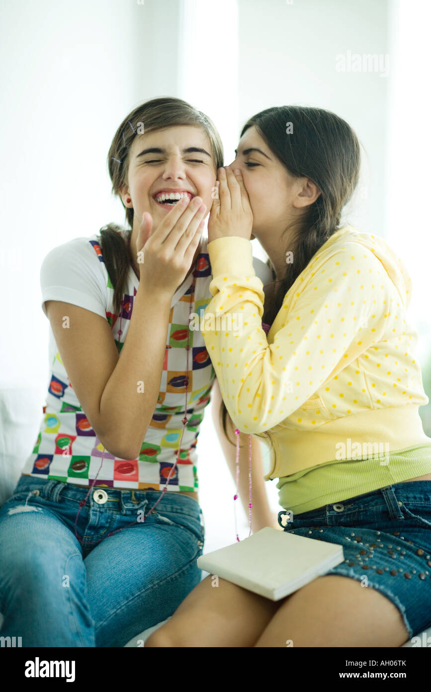 Young female friends, one whispering while the other laughs - Stock Image