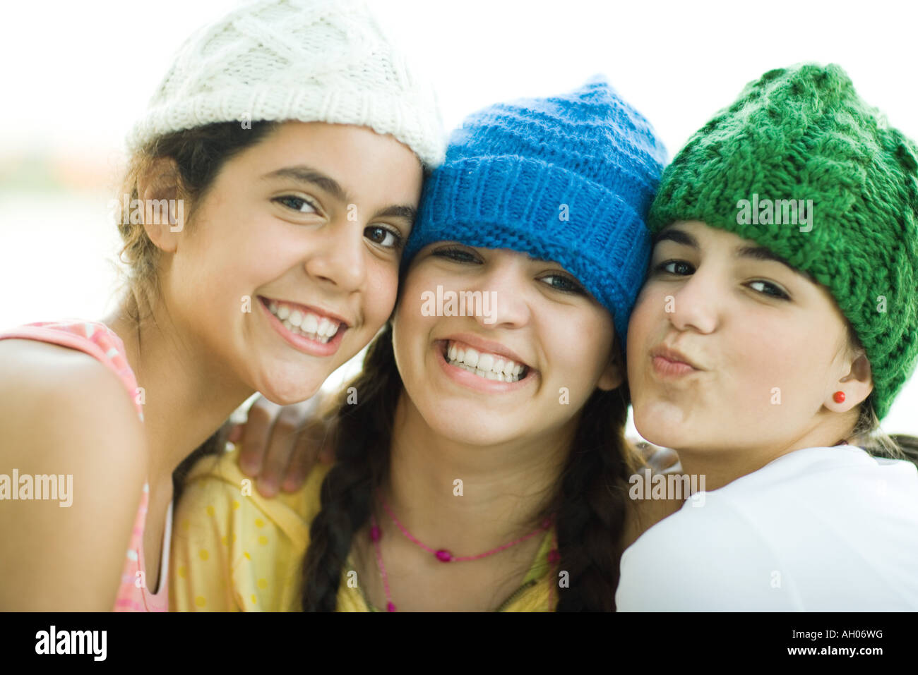 Young female friends wearing knit hats, smiling at camera - Stock Image