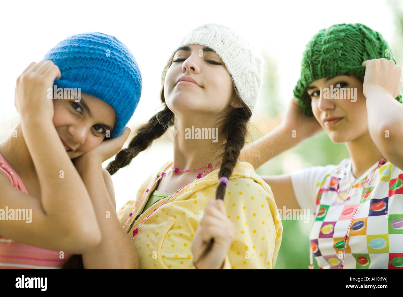 Young female friends wearing knit hats, looking at camera - Stock Image