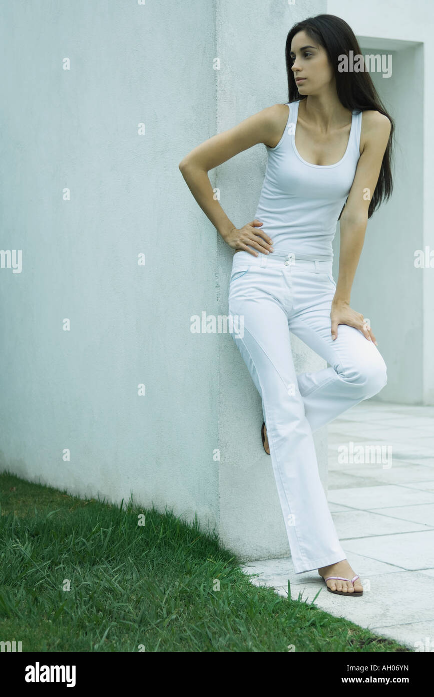 Woman standing, leaning against wall, hand on hip, looking away, full length Stock Photo