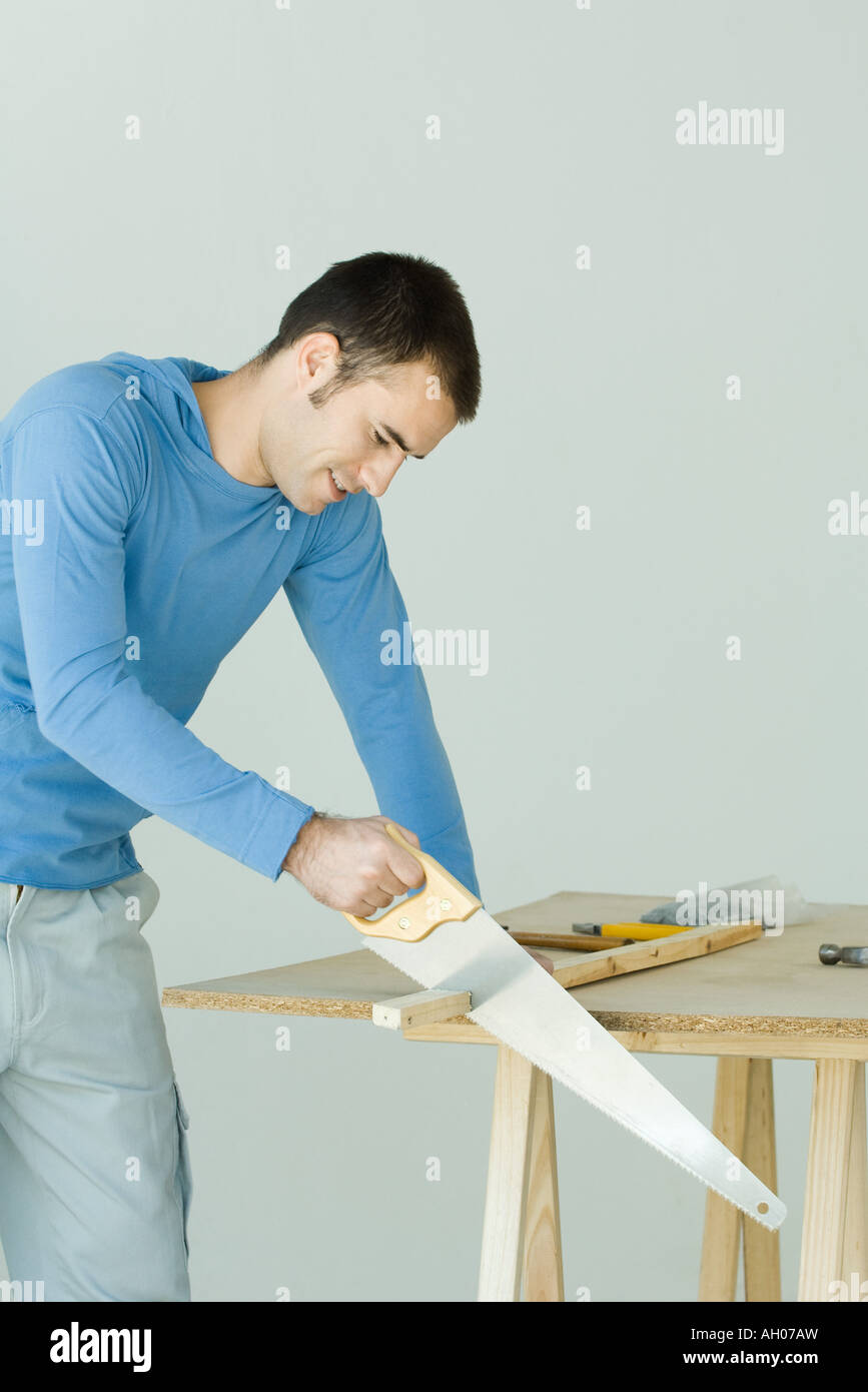 Improvement do it yourself handyman project projects stock photos man sawing wood plank stock image solutioingenieria Gallery