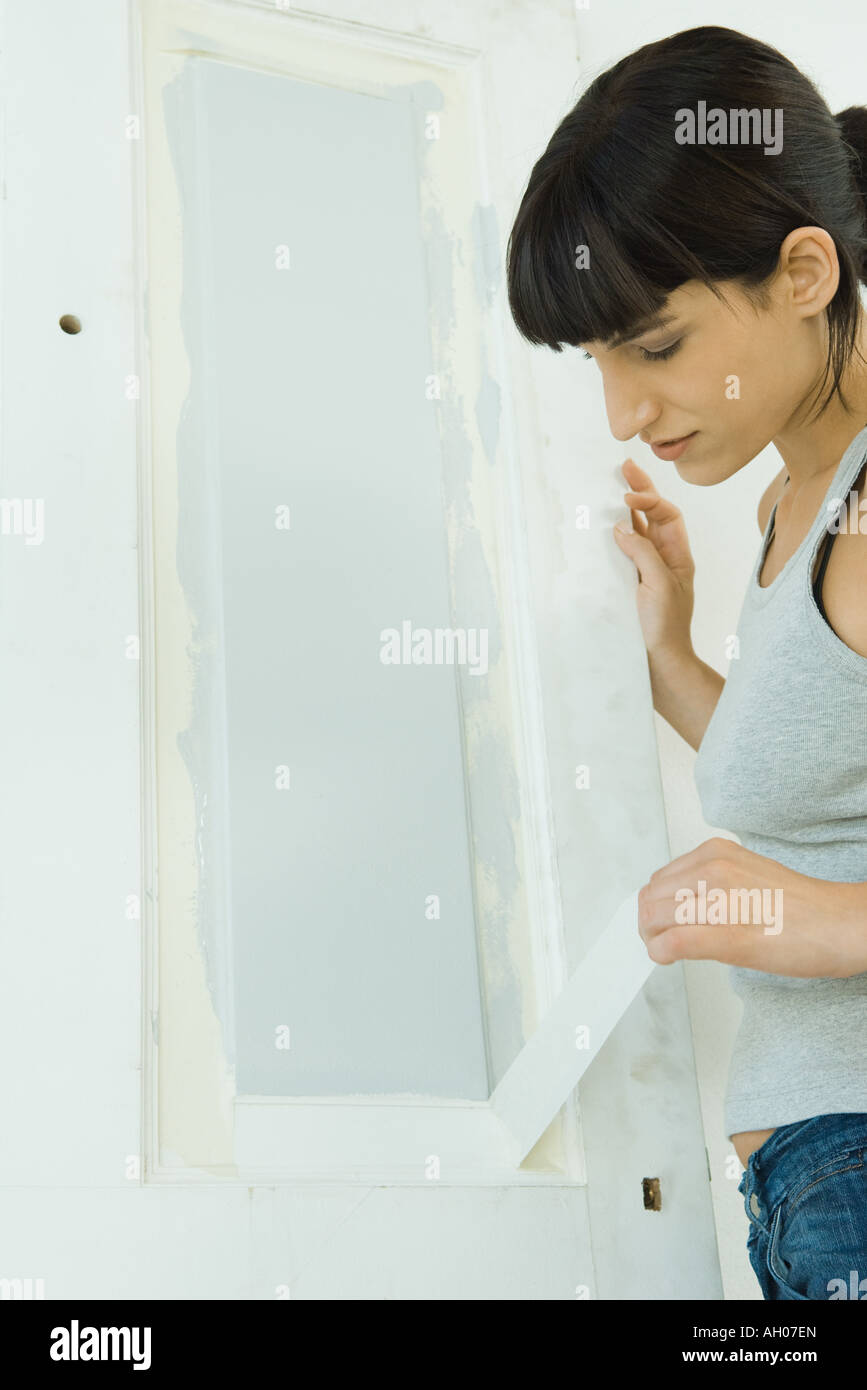 Woman removing masking tape from freshly painted woodwork on door - Stock Image