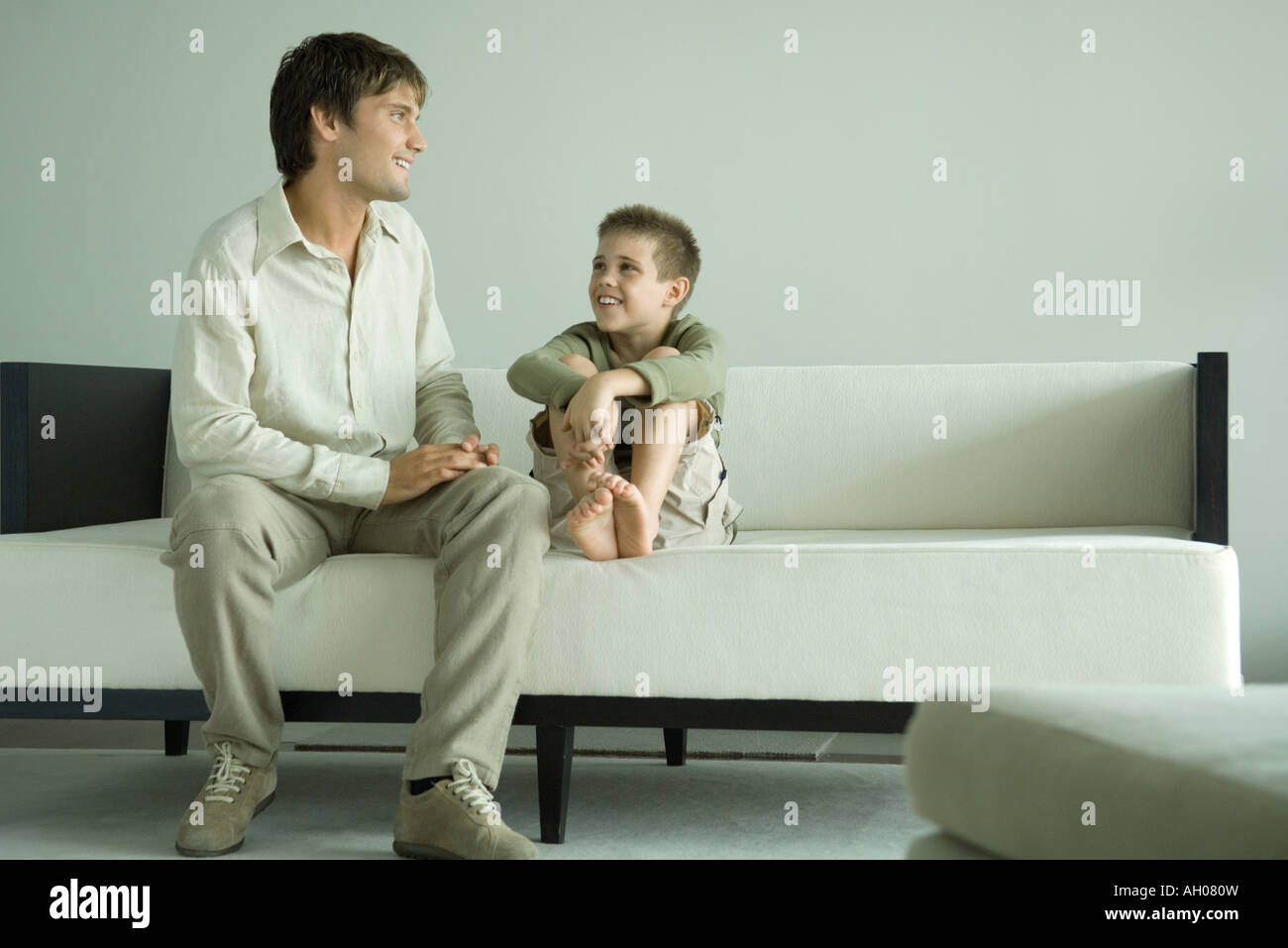 Boy and father sitting on sofa, talking - Stock Image