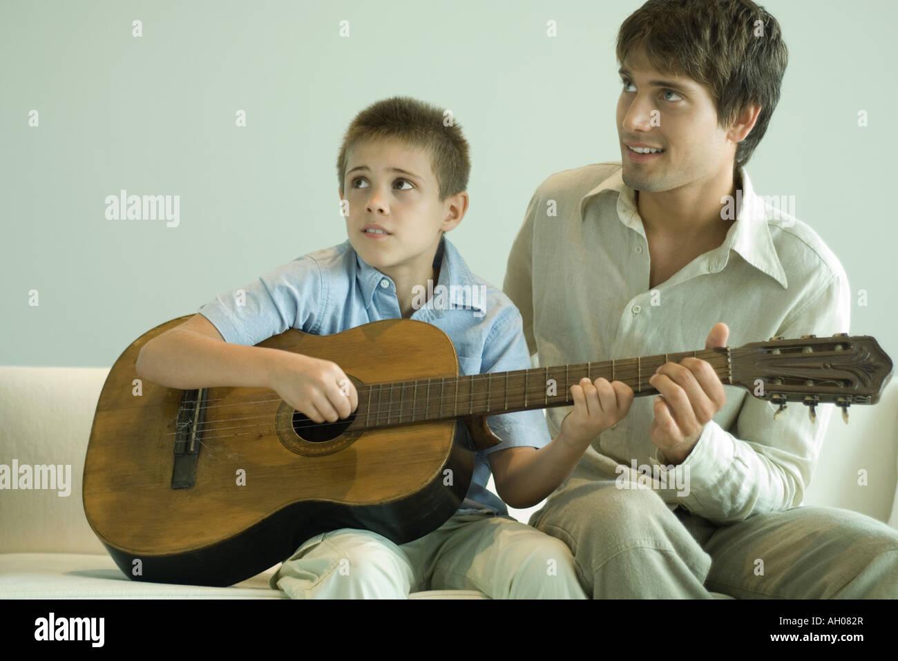 Man teaching boy to play the guitar Stock Photo