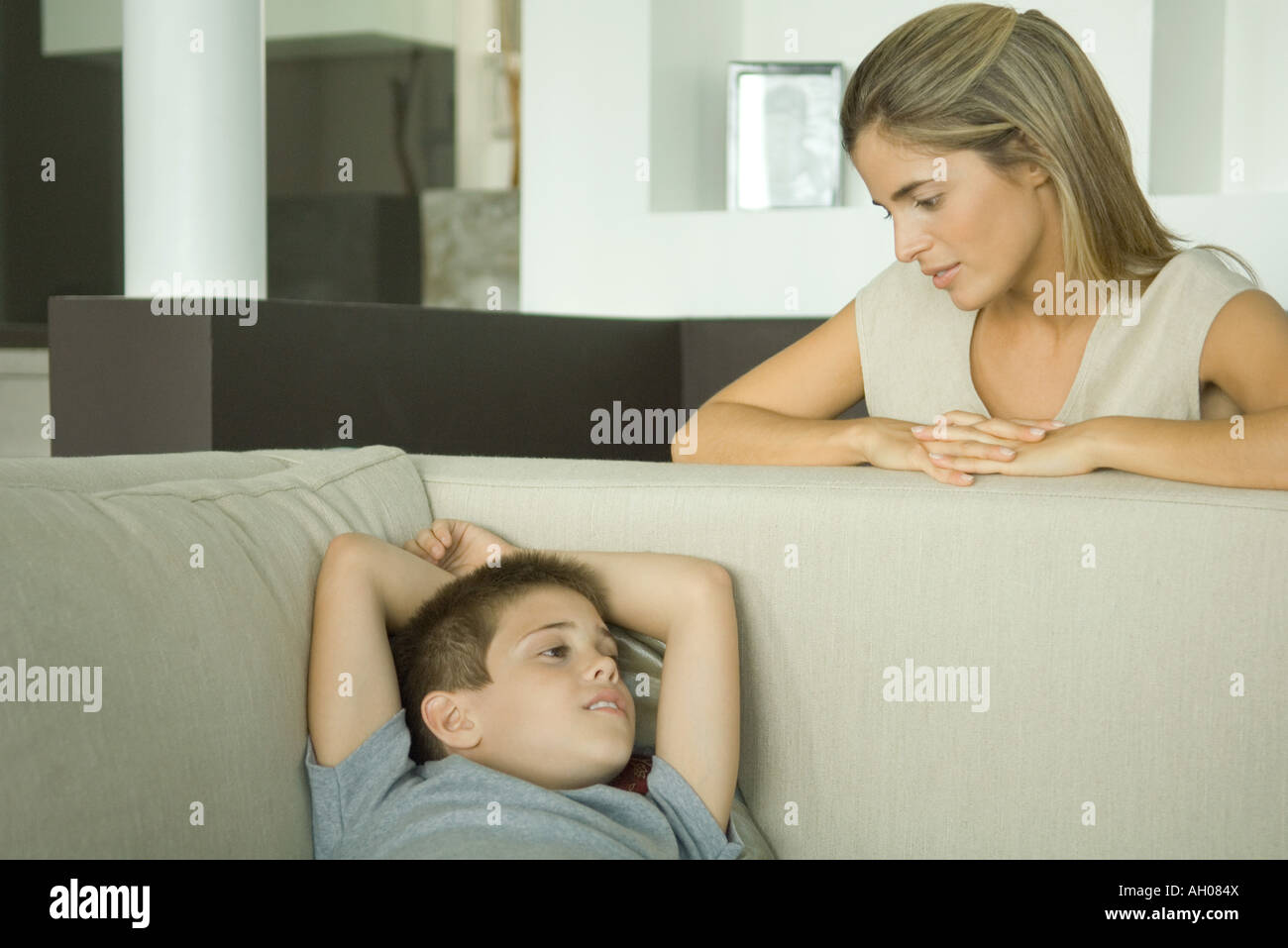 Boy lying on sofa talking to mother looking down at him - Stock Image