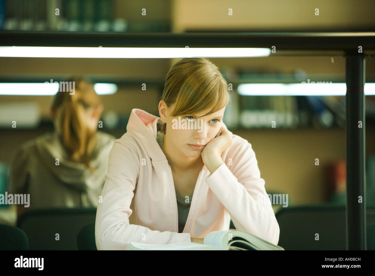 Young woman studying in university library, holding head, looking away - Stock Image
