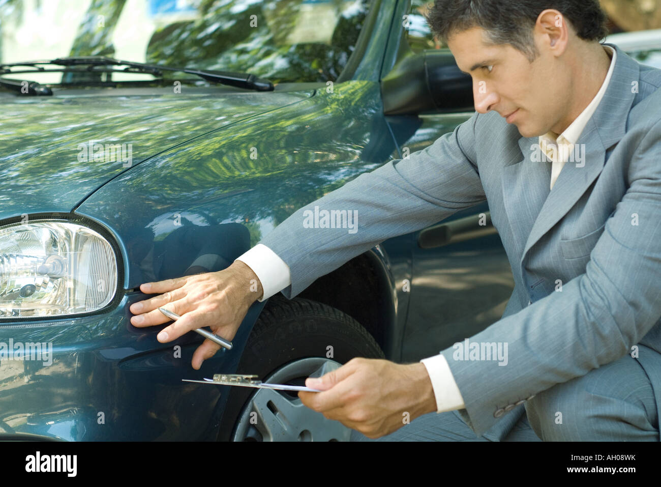 Mature man in suit inspecting car - Stock Image