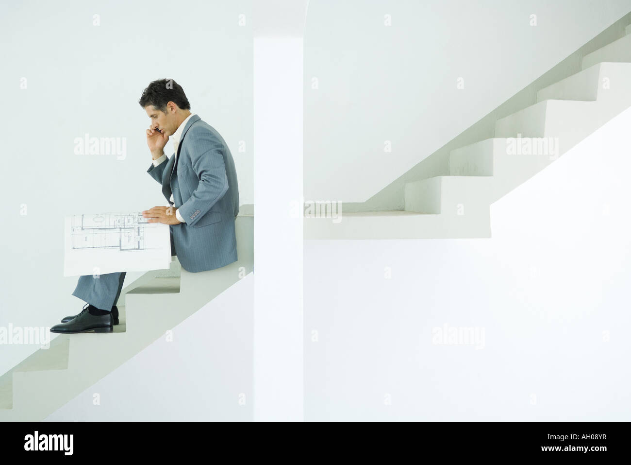 Man In Suit Sitting On Stairs Looking At Blueprints Using Cell