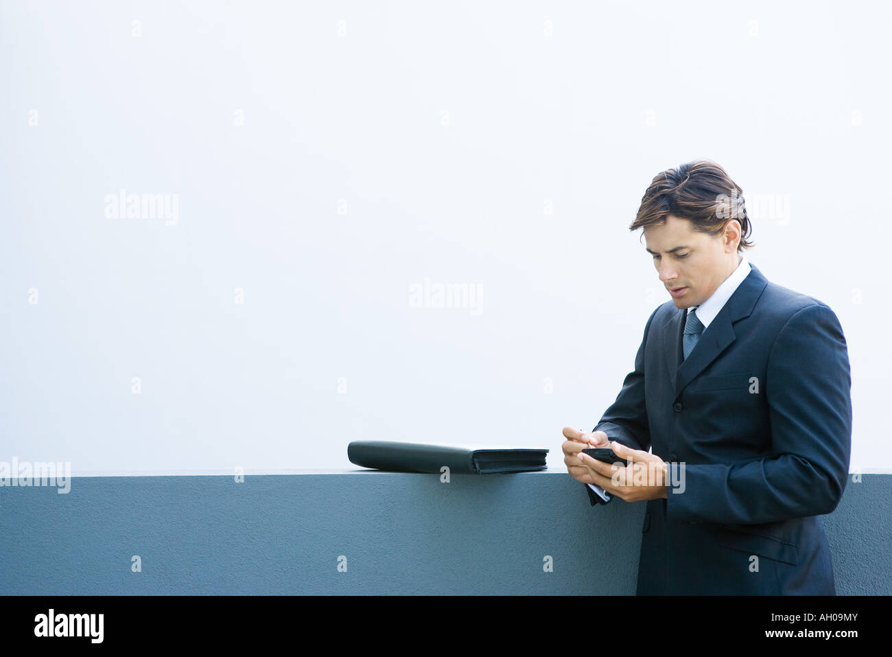 Young businessman using palmtop, looking down - Stock Image