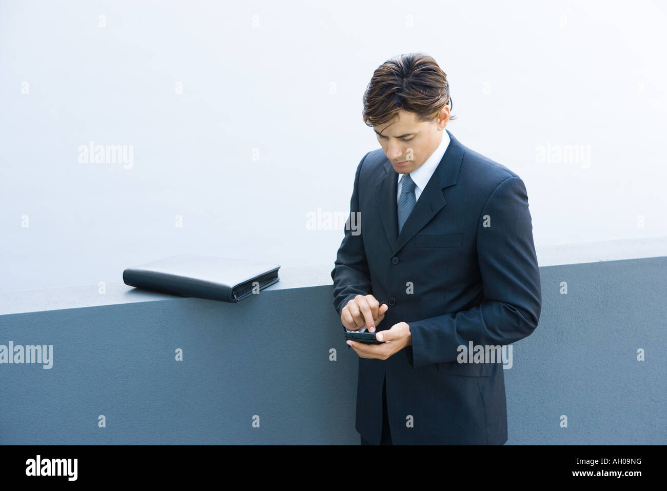 Young businessman using palmtop, looking down, high angle view - Stock Image