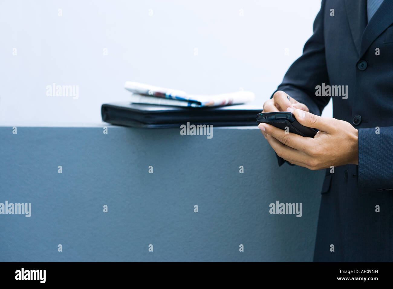 Businessman using palmtop, side view, cropped view of hands - Stock Image