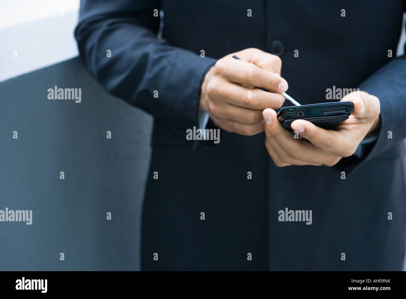 Businessman using palmtop, cropped view of hands - Stock Image