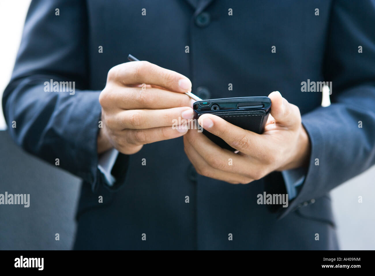 Businessman using palmtop, cropped view - Stock Image