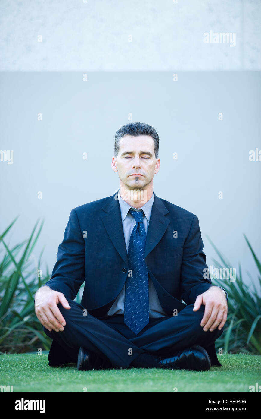 Businessman sitting on ground, meditating, eyes closed, full length portrait Stock Photo