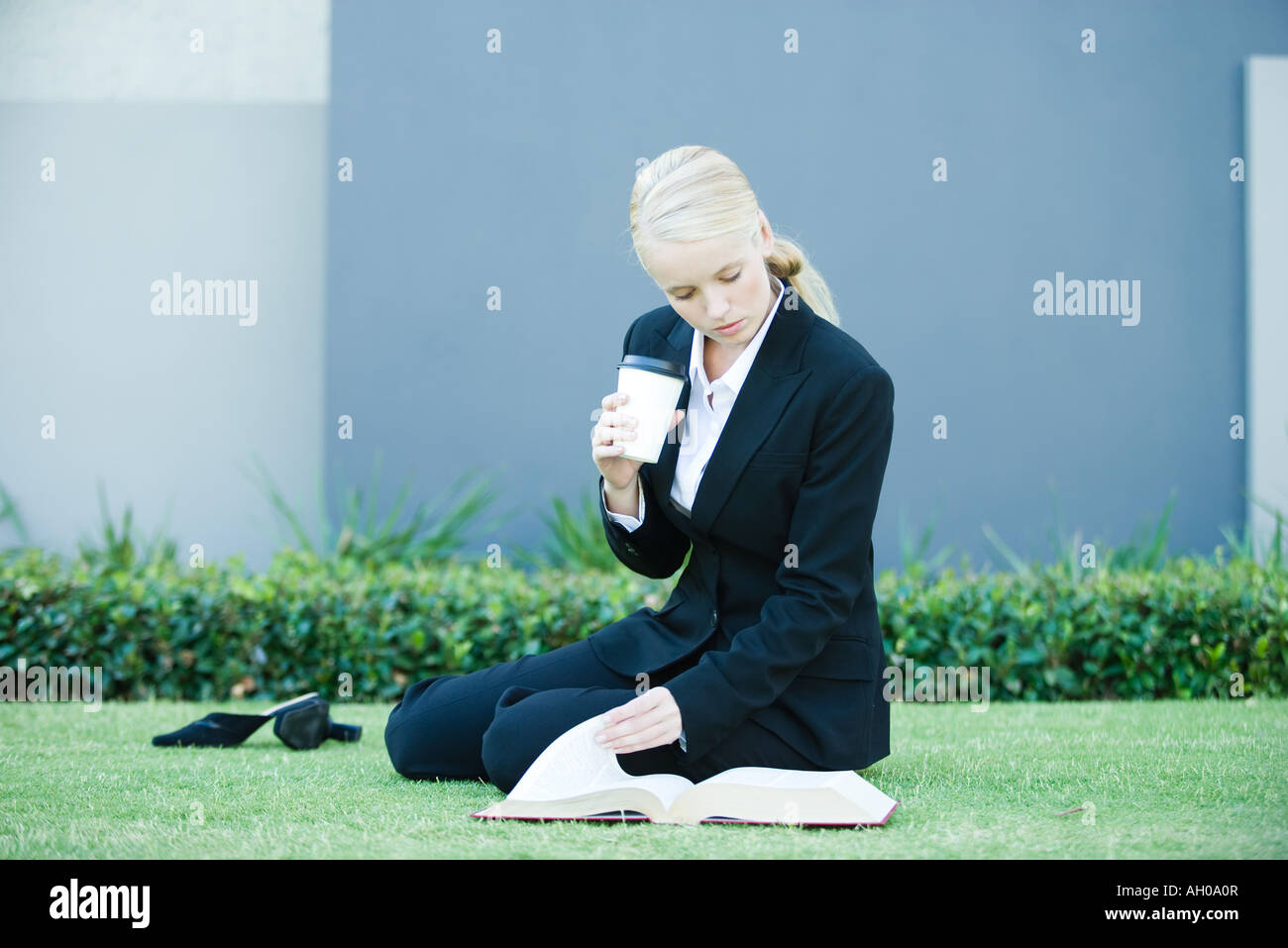 Young businesswoman sitting on the ground outdoors, reading book, holding hot beverage - Stock Image