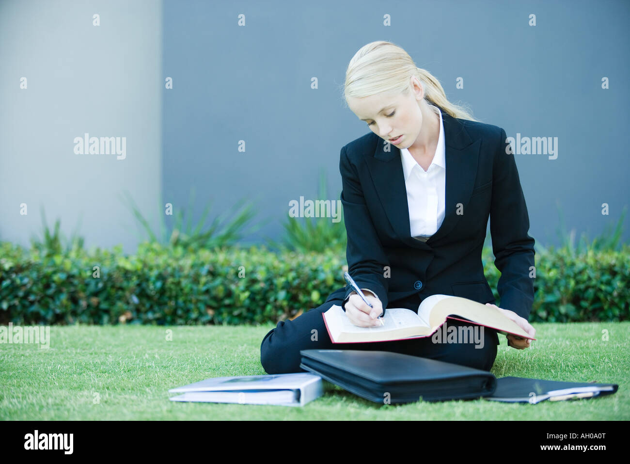 Young businesswoman sitting on the ground outdoors, reading book, holding pen - Stock Image