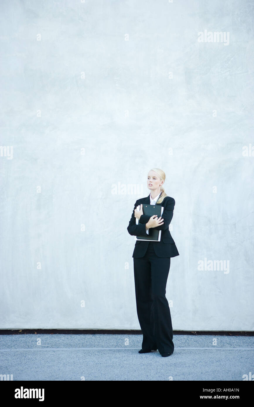 Young businesswoman standing, arms folded, full length - Stock Image
