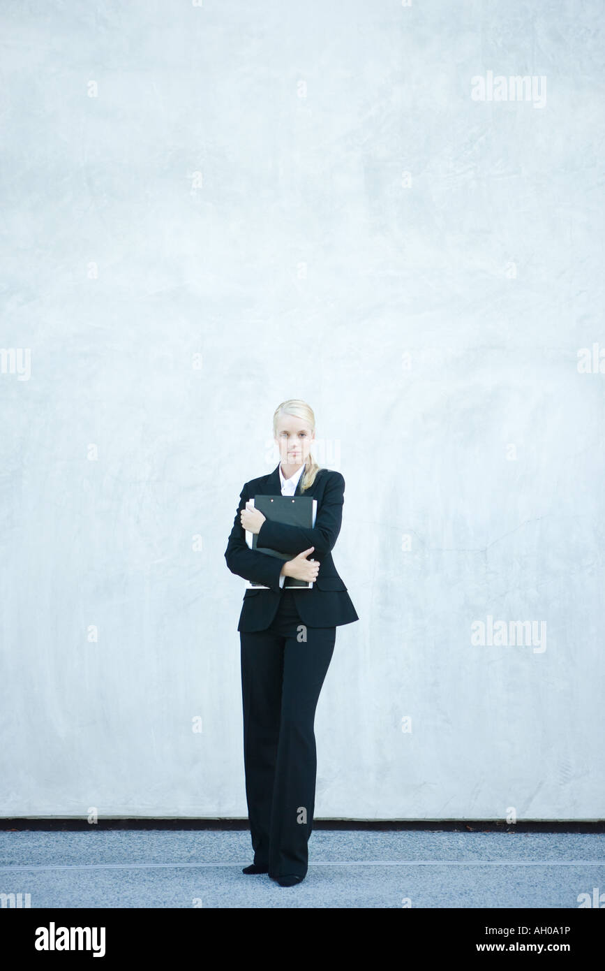 Young businesswoman standing, arms folded, looking at camera, full length - Stock Image