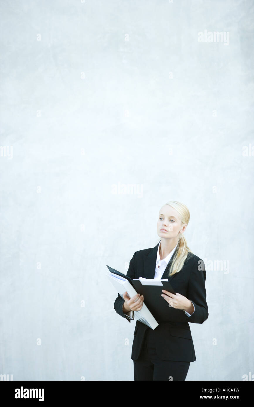 Young businesswoman standing, holding file, looking away - Stock Image