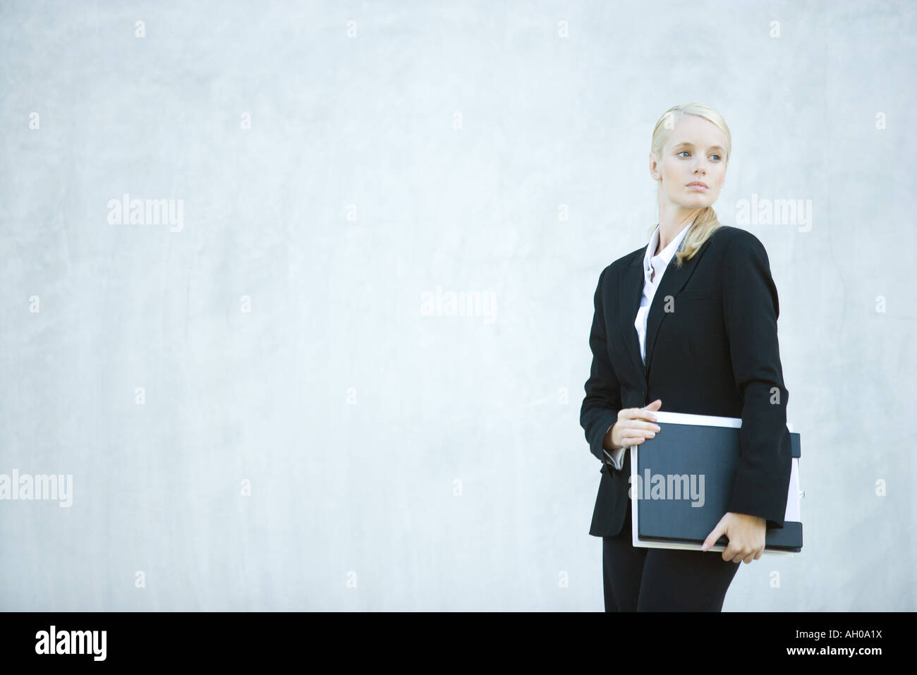 Young businesswoman standing, holding file, looking over shoulder - Stock Image