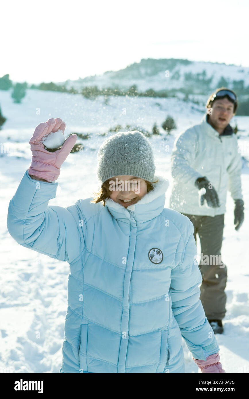 Brother and sister throwing snowballs, girl's eyes closed Stock Photo