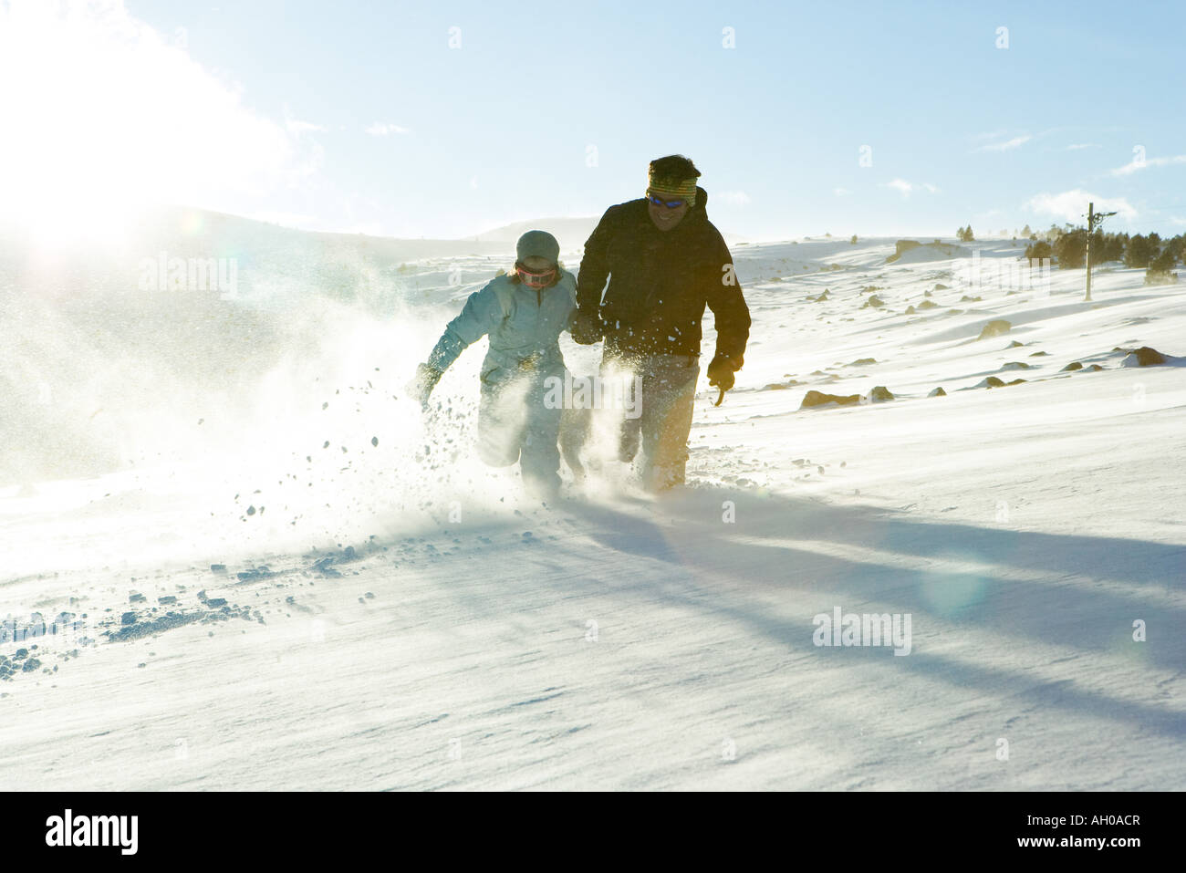 Father and daughter running in snow together, full length - Stock Image