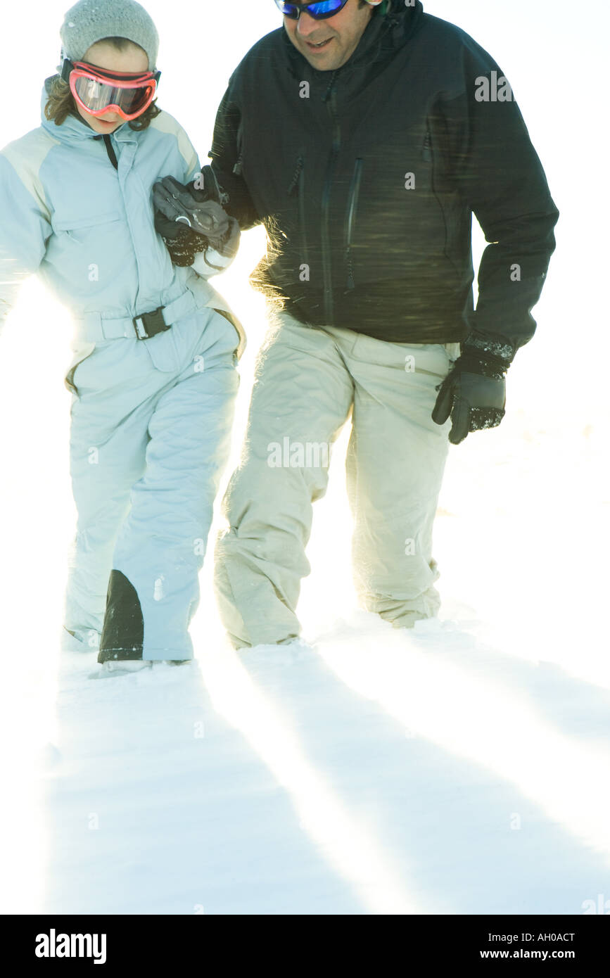 Father and daughter walking in snow together, holding hands, cropped view - Stock Image