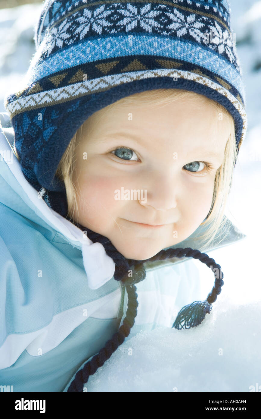 Toddler girl smiling at camera, dressed in winter clothing, portrait - Stock Image