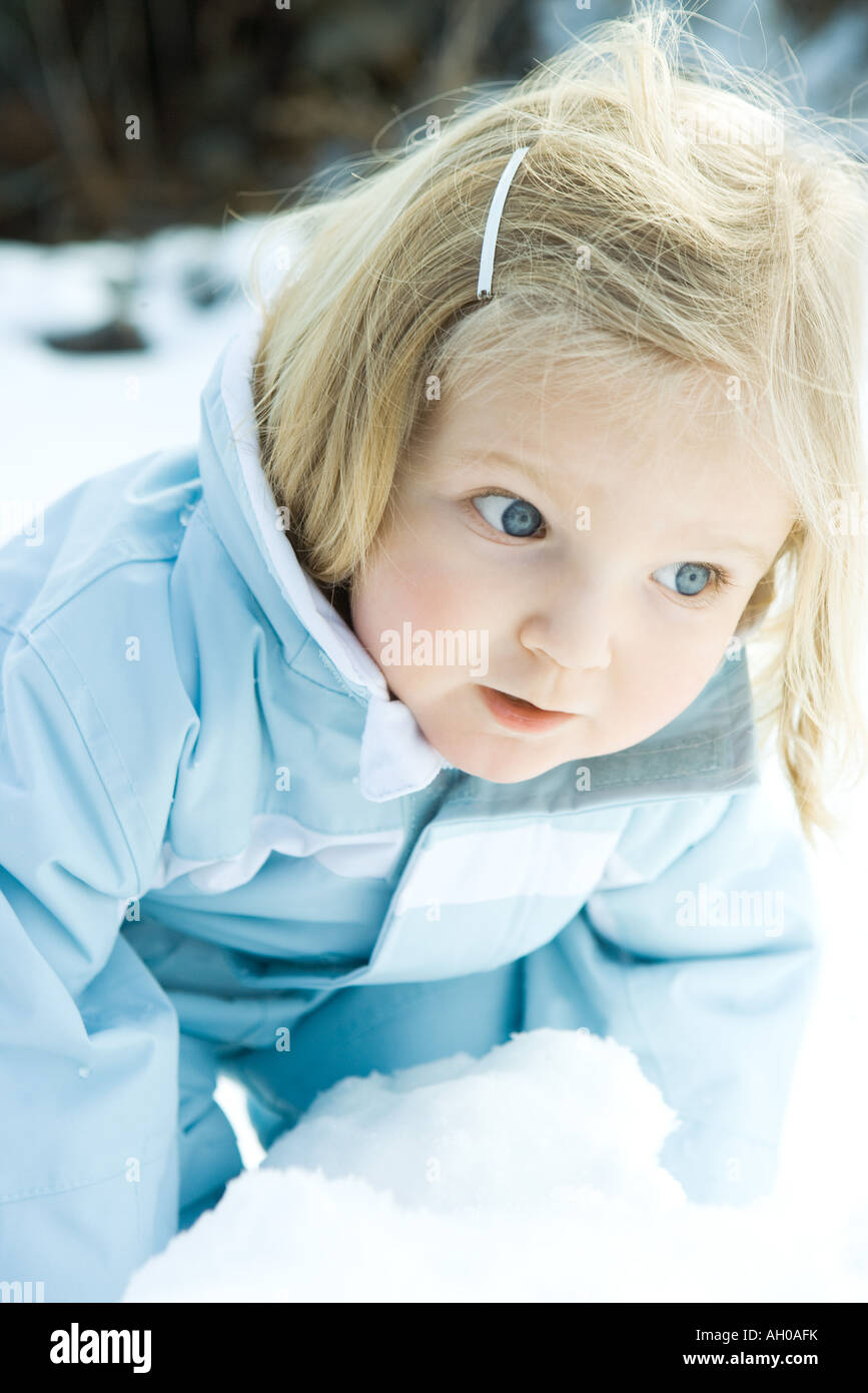 Toddler girl bending over snow, looking away - Stock Image