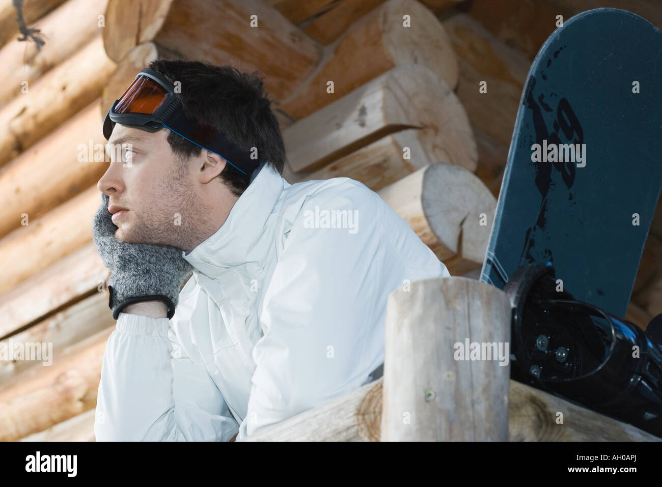 Young man in ski gear standing against deck of log cabin, leaning on rail Stock Photo