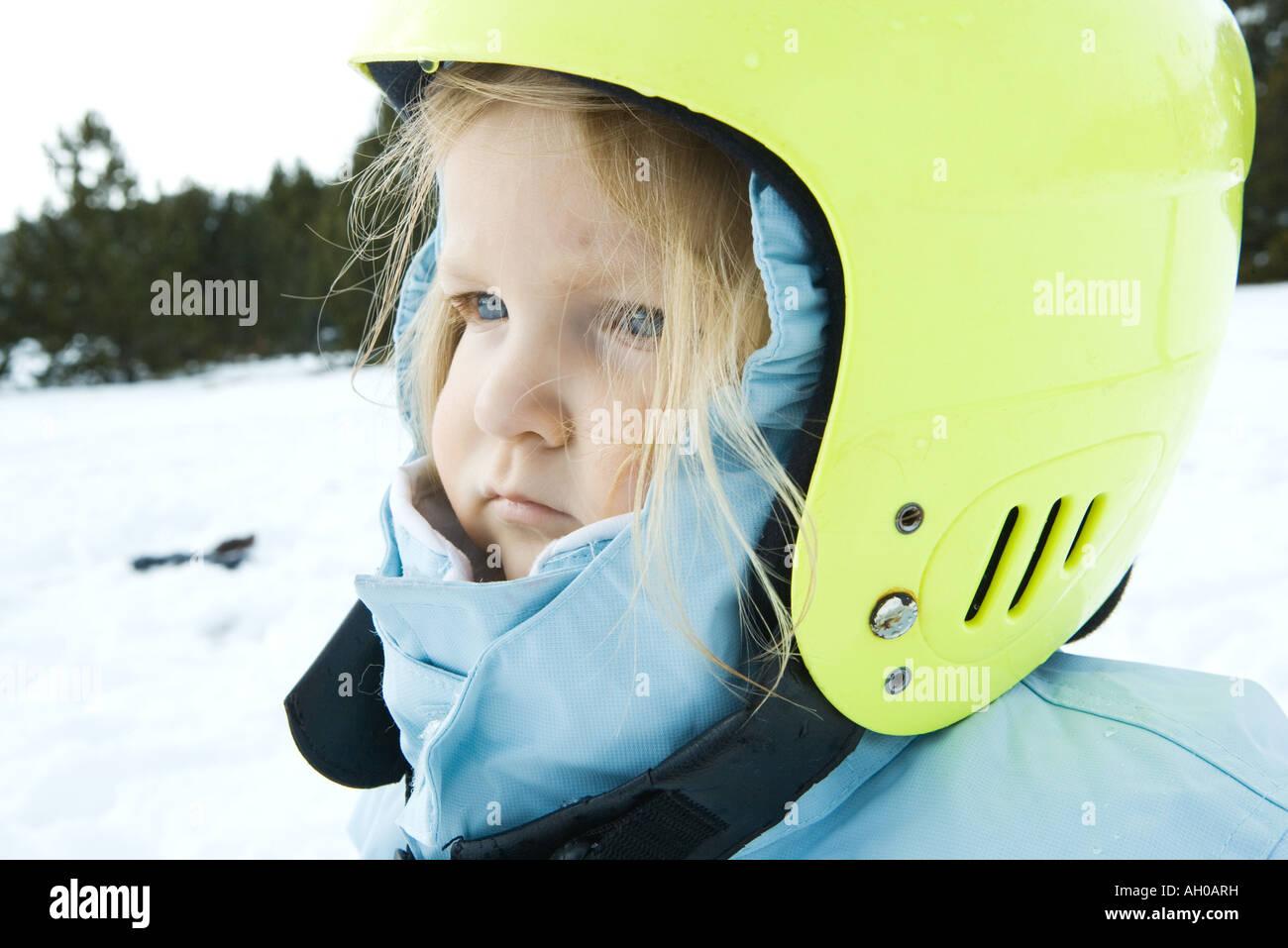 Toddler girl wearing winter coat and helmet, in snowy landscape, portrait - Stock Image