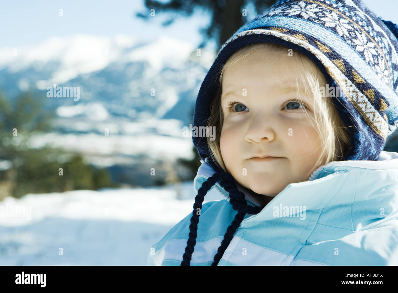 Toddler girl wearing winter clothes in snowy landscape, portrait - Stock Image