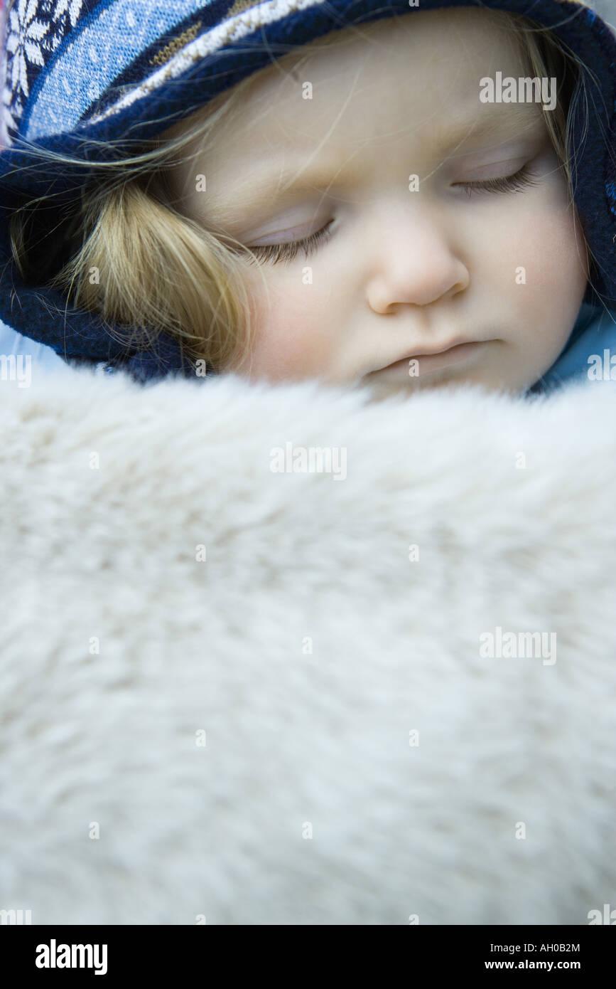 Toddler girl, sleeping under fur blanket, portrait - Stock Image