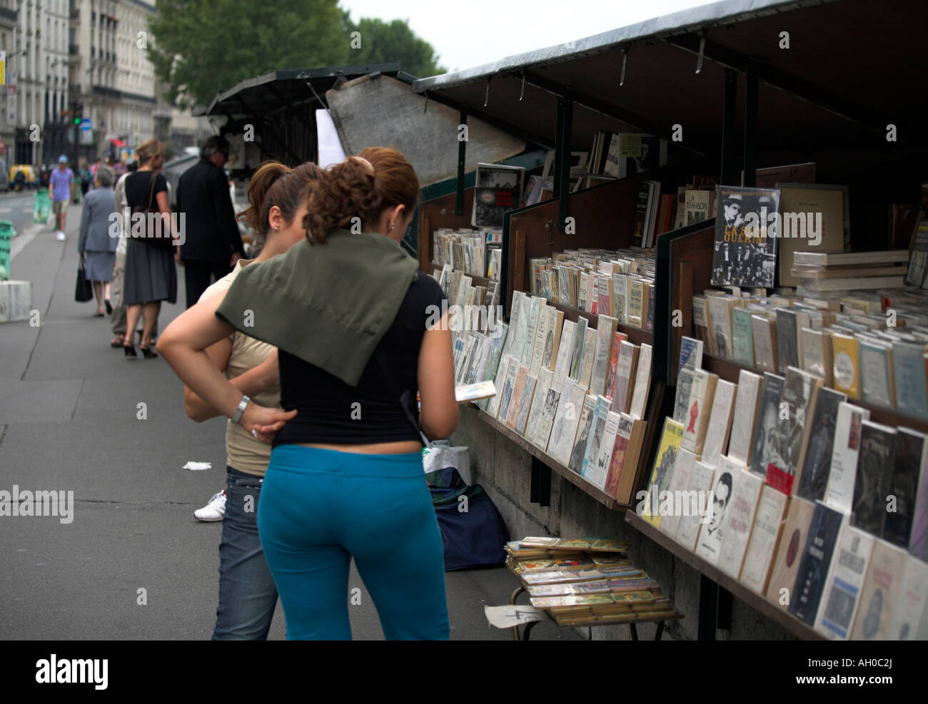 Woman browsing at a bouquinists book seller on the left bank of the River Seine Paris - Stock Image