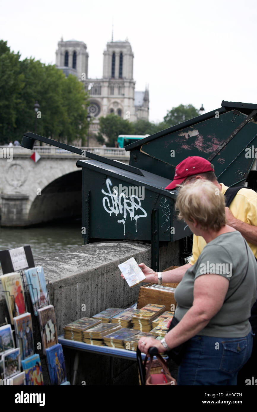 Tourists browsing at a bouquinists book seller on the left bank of the River Seine Paris - Stock Image