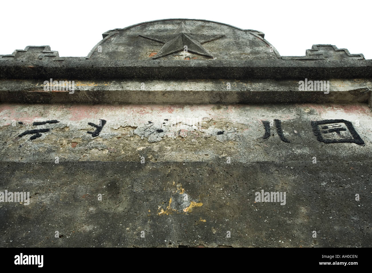 Entranceway with worn Chinese script and star, cropped, low angle view - Stock Image