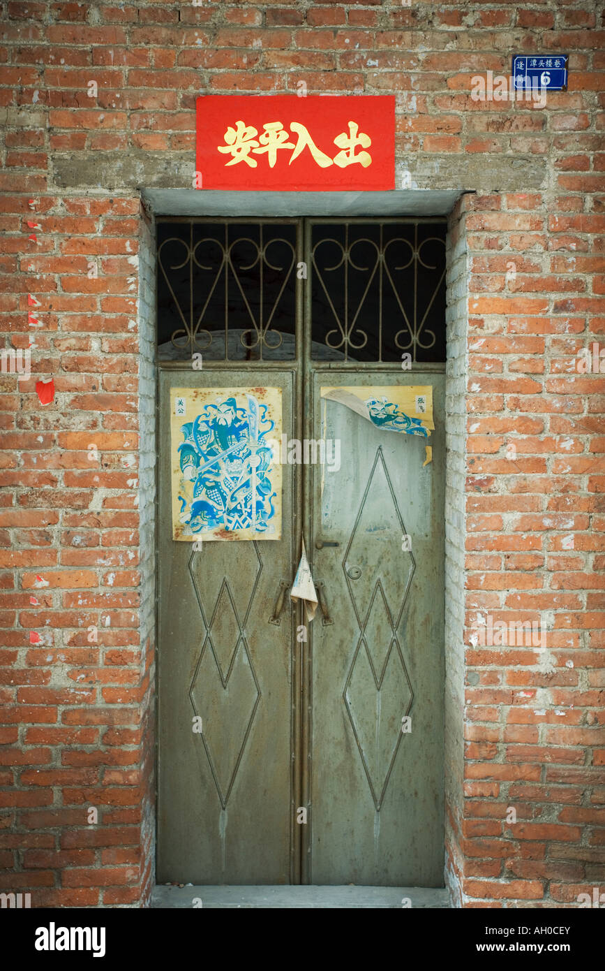 Closed doors with posters on door and banner overhead, China - Stock Image