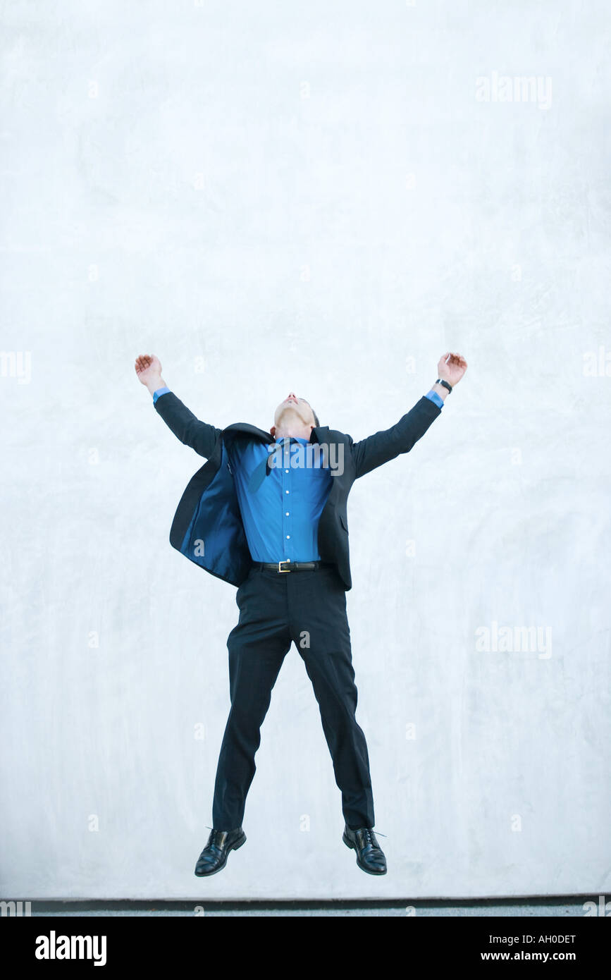 Businessman jumping in air, full length - Stock Image