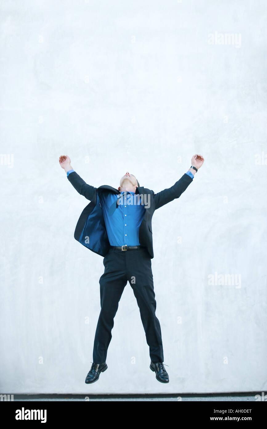 Businessman jumping in air, full length - Stock Image