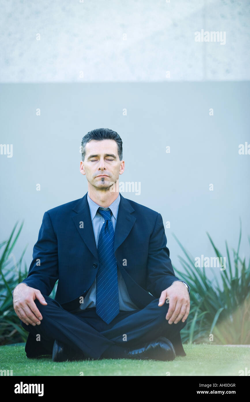 Businessman sitting cross-legged on grass, eyes closed Stock Photo