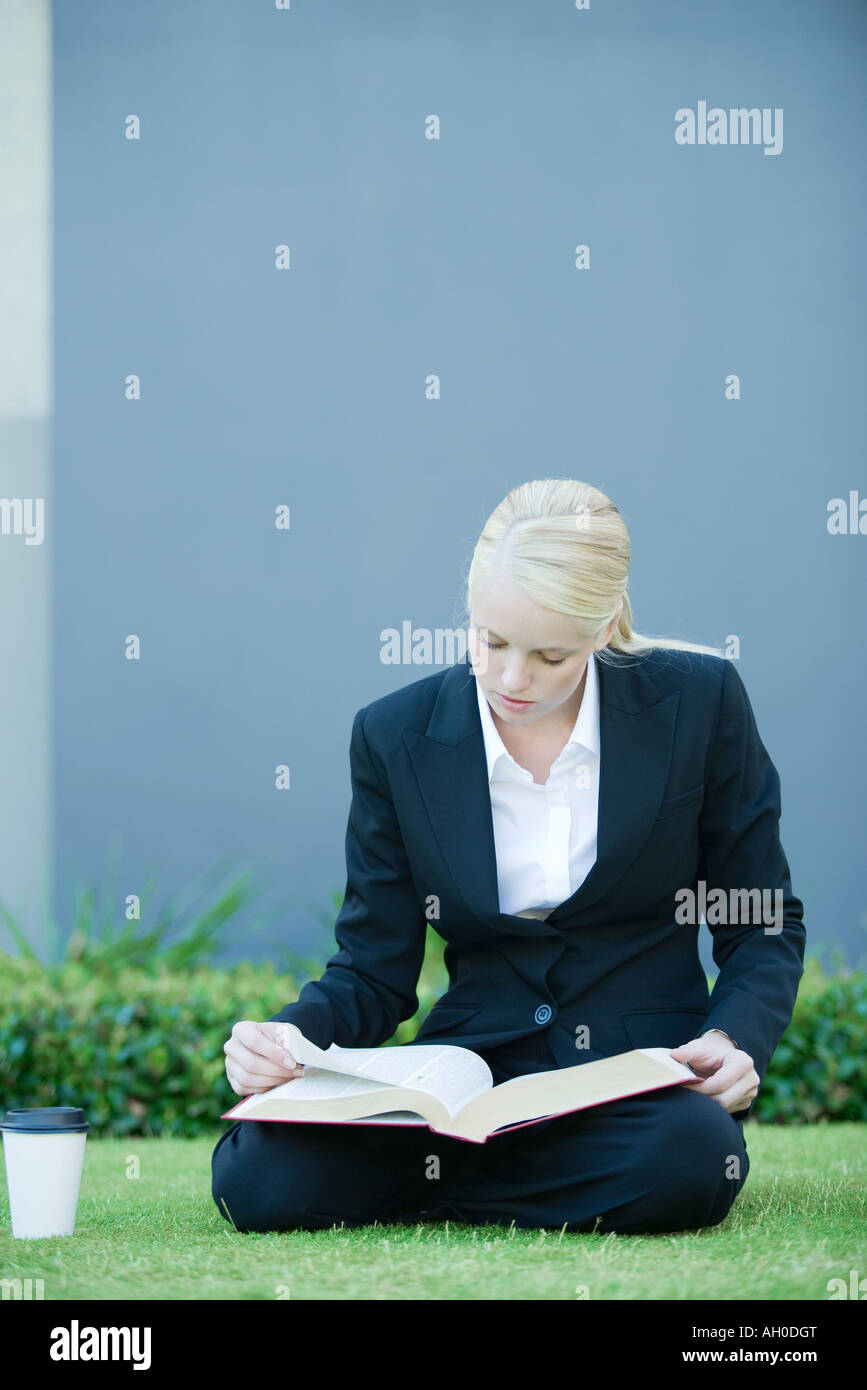 Businesswoman sitting on grass reading book, coffee cup nearby - Stock Image