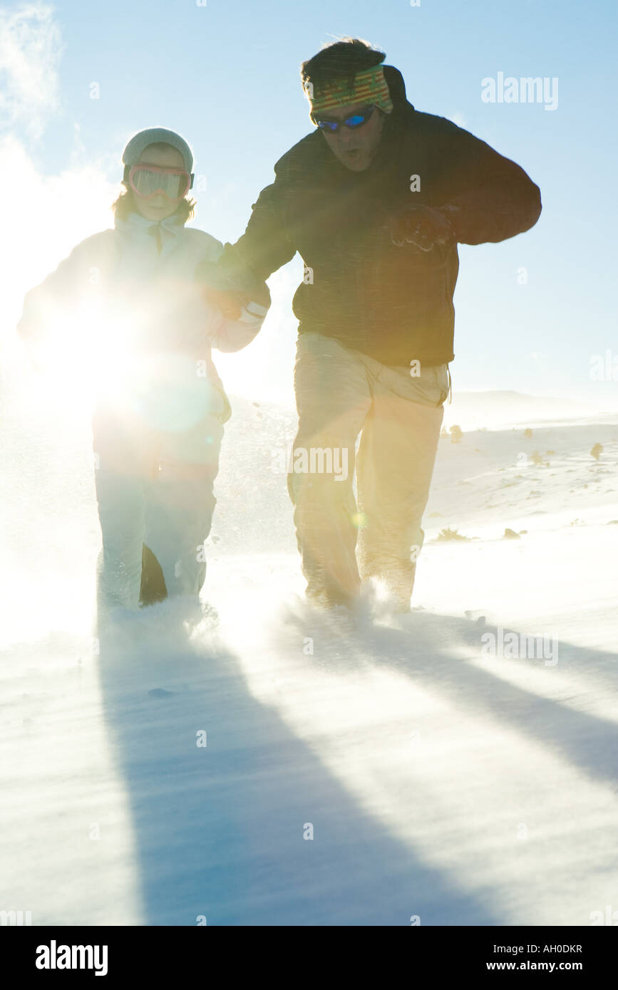 Father and daughter running in snow, dressed in winter clothing, full length - Stock Image